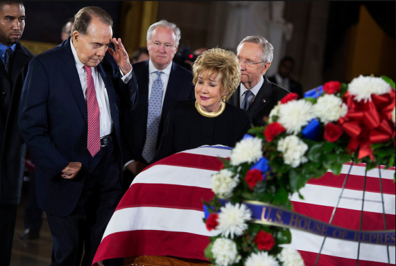 """Former Sen. Bob Dole, R-Kan., salutes the casket of the late Sen. Daniel Inouye, D-Hawaii, as his body lies in state in the Capitol rotunda, as Dole's wife, former Sen. Elizabeth Dole, R-N.C., looks on. Bob Dole and Inouye knew each other since they were recovering from World War II battle wounds. Dole was assisted to the casket saying """"I wouldn't want Danny to see me in a wheelchair.""""  (Photo By Tom Williams/CQ Roll Call)"""