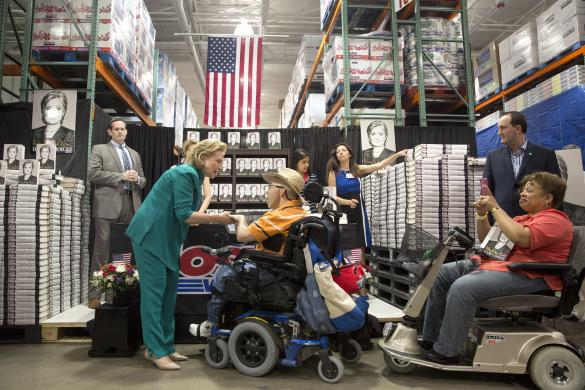 """Former U.S. Secretary of State Hillary Clinton greets people as she signs copies of her book """"Hard Choices"""" at a Costco store in Arlington, Virginia"""