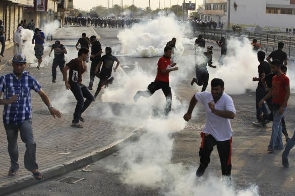 Anti-government protesters take cover from tear-gas fired by the police as they clash in the village of Sitra