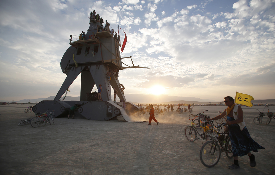 """Participants interact with the Alien Siege Machine during the Burning Man 2014 """"Caravansary"""" arts and music festival in the Black Rock Desert of Nevada"""