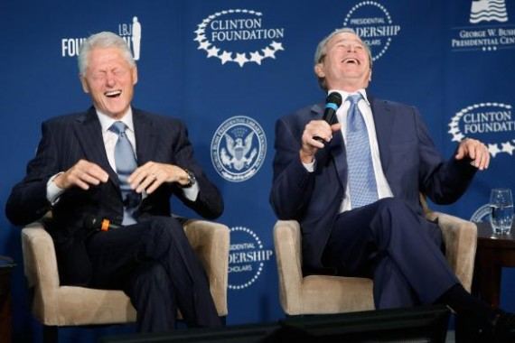 Former U.S. presidents Bill Clinton and George W. Bush laugh on stage during a Presidential Leadership Scholars program event at the Newseum in Washington