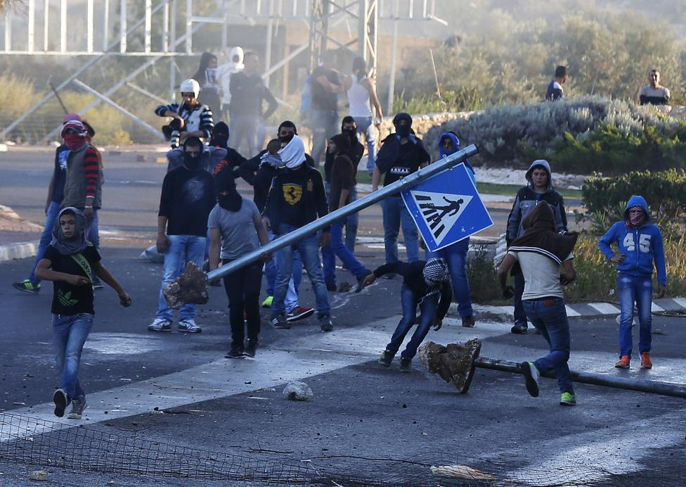 Israeli Arab youths clash with Israeli police at the entrance to the town of Kfar Kanna, in northern Israel