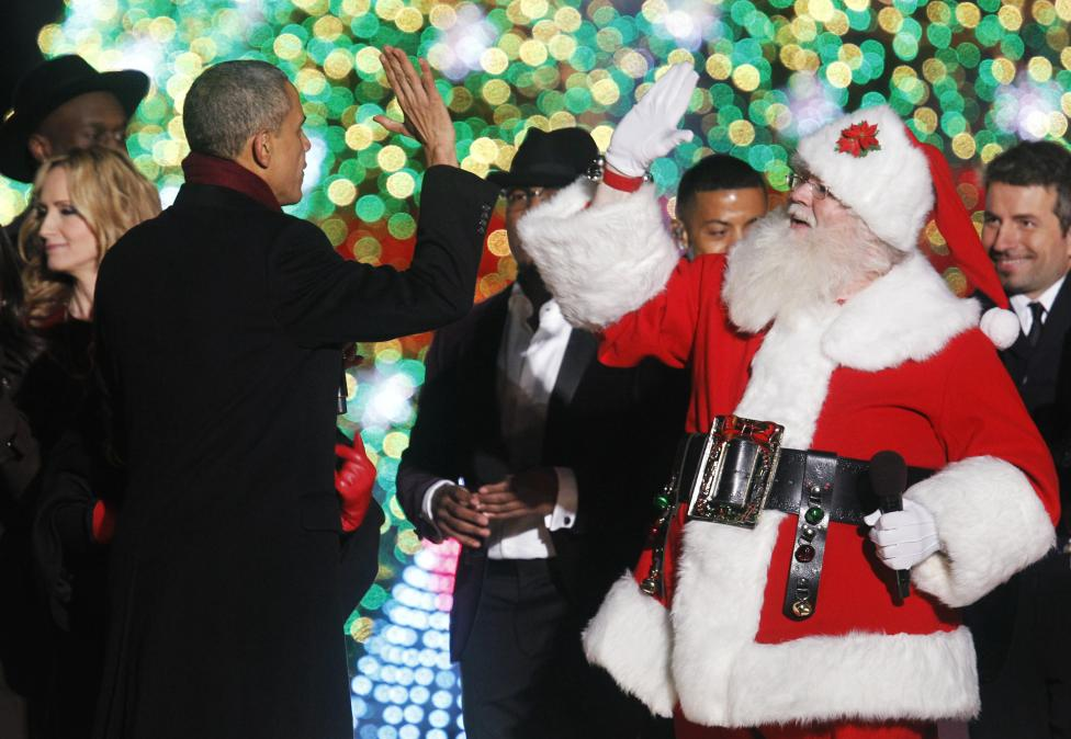 U.S. President Barack Obama gives a high five to a man dressed as Santa Claus during the 92nd annual National Christmas Tree Lighting on the Ellipse in Washington