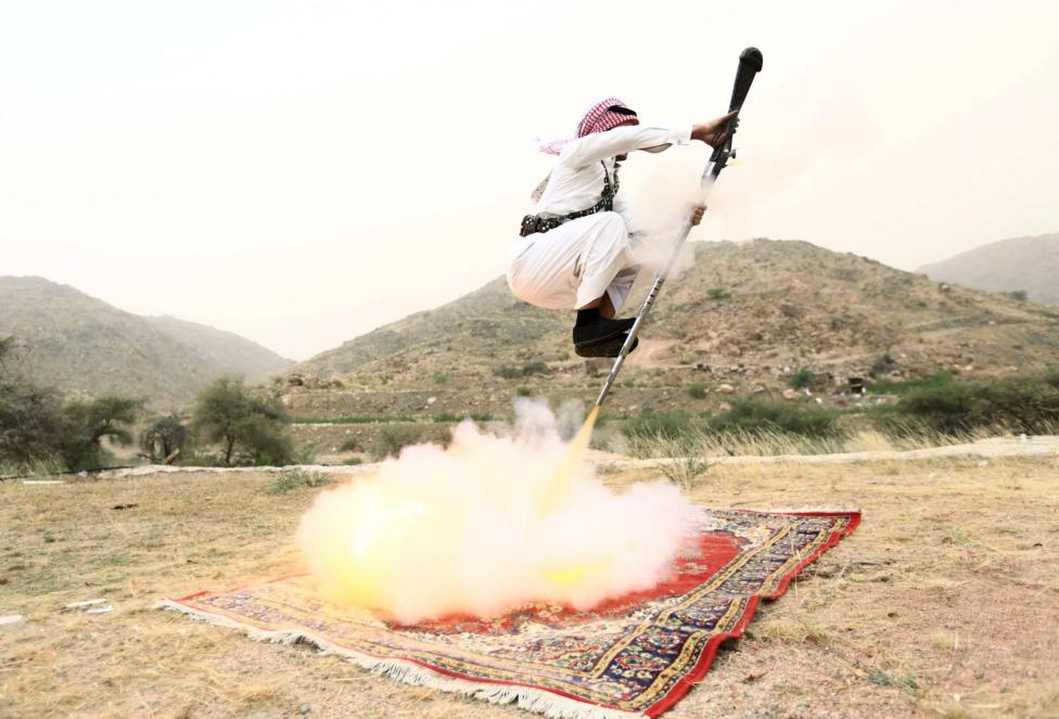 Man fires a weapon as he dances during a traditional excursion near the western Saudi city of Taif