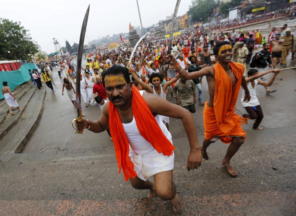 Sadhus or Hindu holy men hold swords as they run towards the banks of Godavari river to take a dip during the Kumbh Mela in Nashik