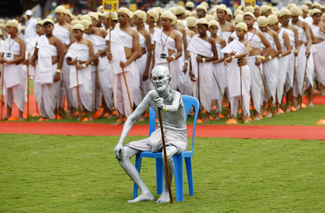 Shri Gopal, a Gandhian or follower of Gandhi's philosophy, sits dressed as India's independence leader Mahatma Gandhi, as he is joined by school children also dressed as Gandhi in an attempt to create a Guinness record, during celebrations to mark Gandhi's birth anniversary in Bangalore, India, Friday, Oct. 2, 2015. 4605 children participated in the event to break the record of largest gathering of people dressed as Gandhi, according to organizers. (AP Photo/Aijaz Rahi)