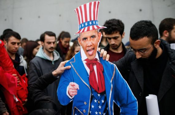 Plainclothes police officers take away an effigy of US President Barack Obama as the members of Turkey Youth Union gather to protest against the upcoming visit of Obama to Turkey mid-November for G20 summit in Antalya, outside the US consulate in Istanbul, Turkey, Sunday, Nov. 8, 2015. (AP Photo/Emrah Gurel)