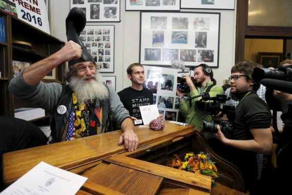 U.S. Democratic presidential candidate Vermin Supreme (L) reacts after filing his declaration of candidacy to appear on the New Hampshire primary election ballot in Concord, New Hampshire, November 20, 2015. To appear on the primary ballot candidates must sign a declaration affirming that they meet the Constitutional requirements to run for President and pay a $1,000 filing fee. REUTERS/Brian Snyder      TPX IMAGES OF THE DAY