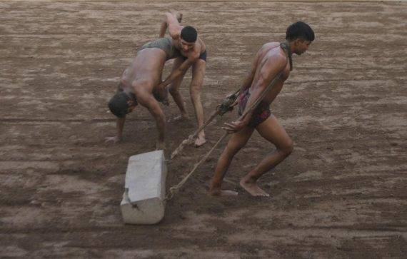 A Pakistani Kushti wrestler prepares the grpund in the ring while others practice during a training session, in Lahore, Pakistan, Tuesday, Jan. 5, 2016. Kushti, an Indo-Pakistani form of wrestling, is several thousand years old and is a national sport in Pakistan. (AP Photo/K.M. Chaudary)
