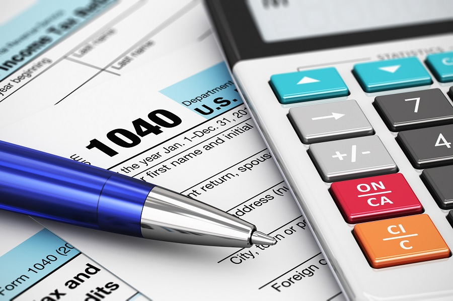 Macro view of 1040 US Tax Form, calculator and ballpoint pen