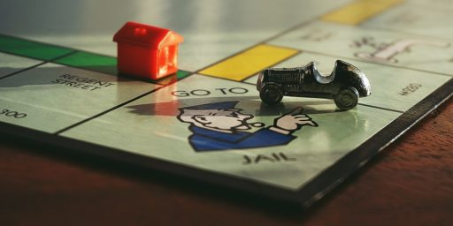 Monopoly board Go Directly to Jail with car and hotel