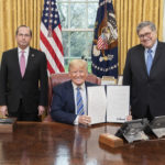 President Donald J. Trump, joined by Health and Human Services Secretary Alex Azar, left, and Attorney General William Barr, displays his signature after signing an Executive Order to Prevent Hoarding and Price Gouging, Monday, March 23, 2020, in the Oval Office of the White House. (Official White House Photo by Shealah Craighead)