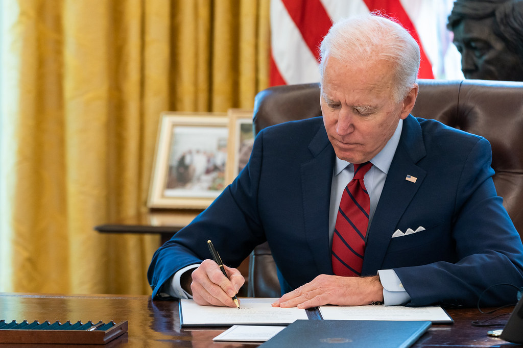 President Joe Biden signs two executive orders on healthcare Thursday, Jan. 28, 2021, in the Oval Office of the White House.